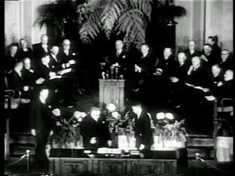 B/W 1949 high angle wide shot man at desk signing NATO pact at United Nations / row of men sit on platform in background