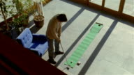 High angle wide shot man practicing putting on indoor green/ making shot/ Solebury, Pennsylvania