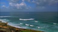 High angle wide shot pan along Old San Juan city wall on Atlantic coast to San Cristobal on cliff / Puerto Rico