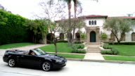 High angle wide shot pan couple in convertible pointing as they drive by mansion / Beverly Hills, California
