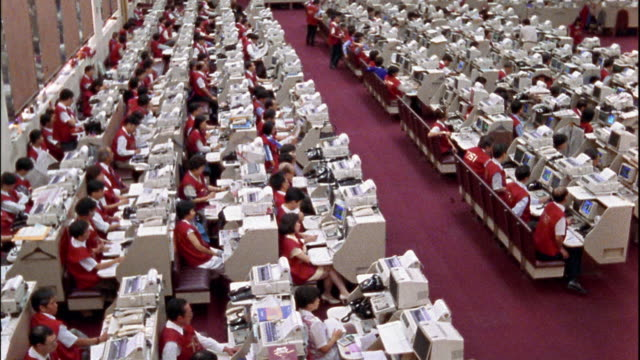 High angle wide shot pan crowd of traders seated in rows at Hong Kong Stock Exchange