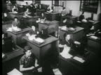 B/W 1939 high angle wide shot rows of women typing on typewriters at desks in office / documentary