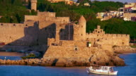 High angle wide shot ruins of castle with boat on Mediterranean Sea in foreground / Rhodes, Greece