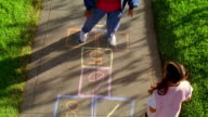 High angle wide shot senior woman playing Hopscotch on sidewalk as young girl claps and watches