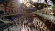 High angle wide shot tilt down crowd of commuters walking in Liverpool Street Station / London, England