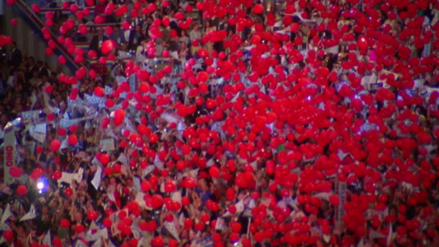 high angle wide shot tilt down red balloons falling on state delegates at Democratic National Convention / Los Angeles
