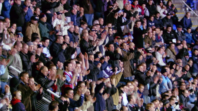 High angle wide shot tilt down tilt up zoom out crowd chanting and clapping during soccer match at Madejski Stadium / Reading, England