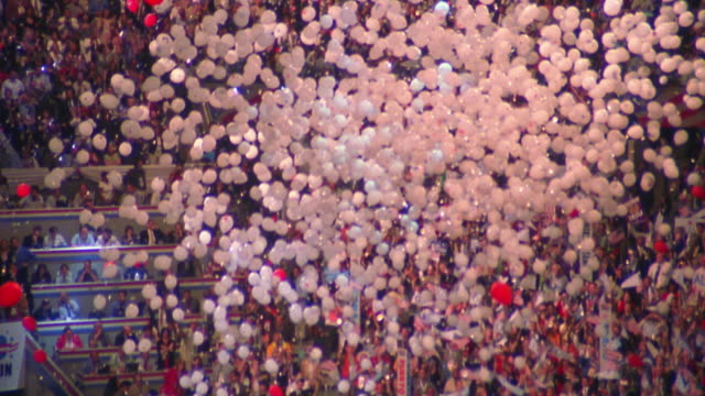 high angle wide shot tilt down white balloons falling on state delegates at Democratic National Convention / Los Angeles