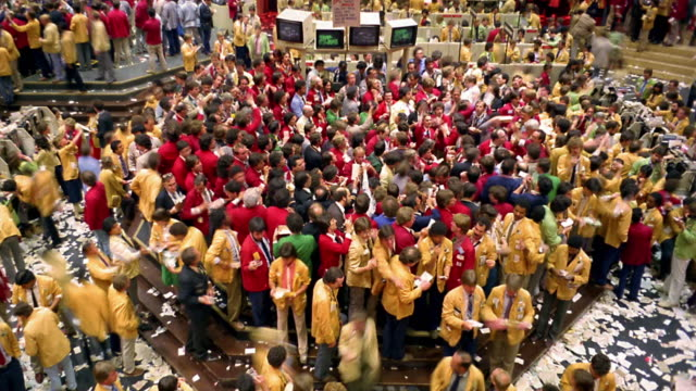 High angle wide shot time lapse crowd of busy stockbrokers gesturing on trading floor of Chicago Mercantile Exchange