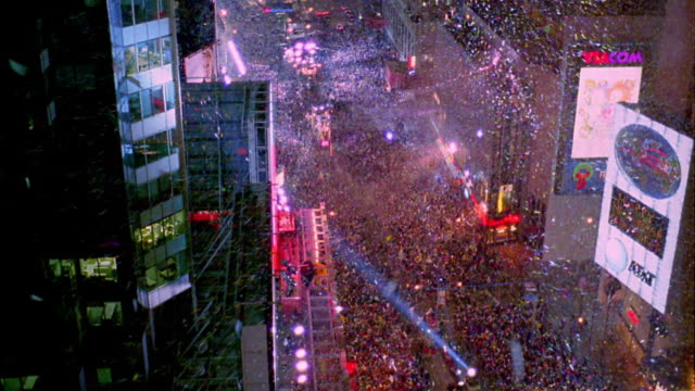 High angle wide shot time lapse large crowds and searchlights in Times Square at night on New Year's Eve / people leave