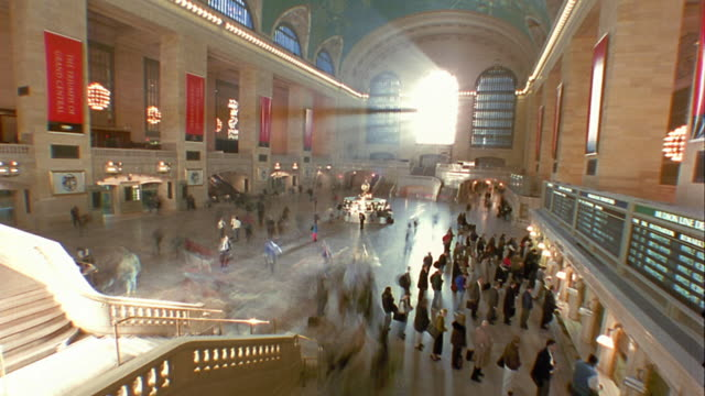 High angle wide shot time lapse people walking through lobby of Grand Central Station with sun shining through window / NYC