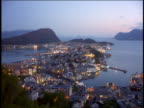 high angle wide shot time lapse small city on peninsula / day to night / Alesund, Norway