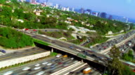 High angle wide shot time lapse traffic on Freeway 405 and overpass with city skyline in background / Los Angeles
