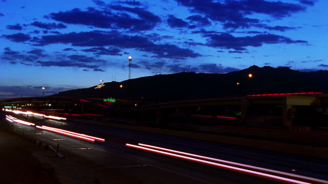 High angle wide shot time lapse traffic on highway with clouds rolling over hill in background / dusk to night / El Paso, Texas