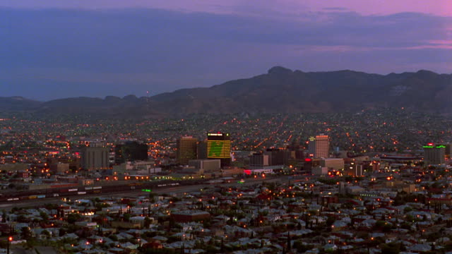 High angle wide shot time lapse traffic on streets of El Paso / dusk to night / Texas