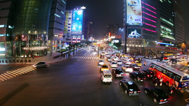 High angle wide shot traffic passing through intersection of Keelung and Xinyi roads at night / Taipei, Taiwan