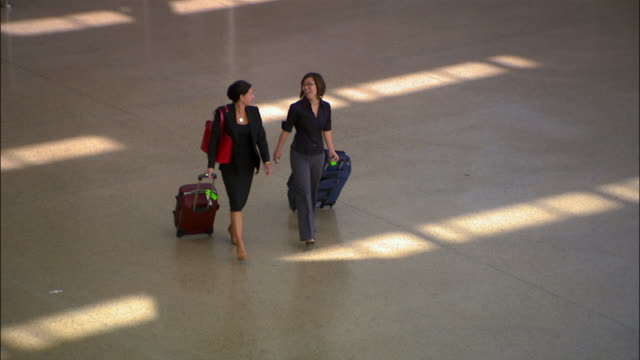 High angle wide shot two businesswomen pulling luggage through airport/ Seattle