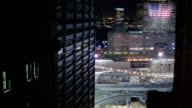 High angle wide shot view of Ground Zero and American flag hung on exterior of World Financial Center at night / NYC