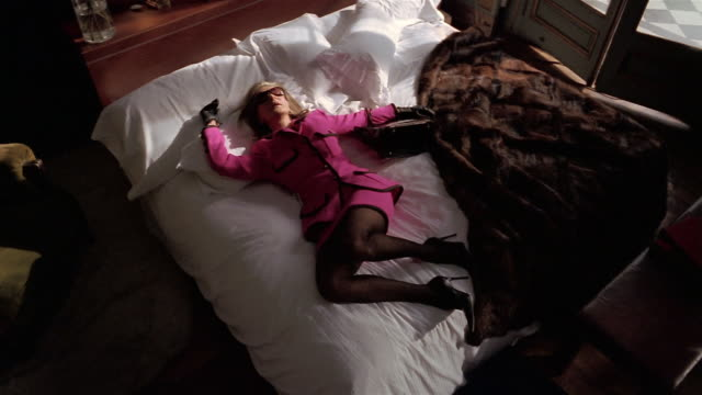 High angle wide shot woman in suit and sunglasses falling onto bed with fur coat thrown on top