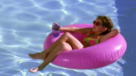 High angle wide shot young girl floating on pink inner tube in pool with boy jumping in and splashing her / Tucson, Arizona