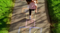 High angle wide shot young girl with pigtails playing hopscotch on sidewalk