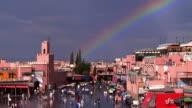 High angle wide shot zoom in Djemma El Fna Square market square beneath rainbow / Marrakesh, Morocco