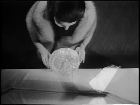 B/W 1956 high angle woman facing mirror modelling plastic crown-like hat / newsreel