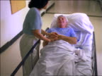 high angle woman talking + holding hand of senior male patient in gurney in hospital corridor