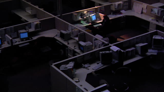 high angle zoom in one woman working late at computer with desk lamp in dark office with cubicles