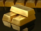 high angle zoom in to extreme close up 24 karat gold bars stacked + in row on black reflective table