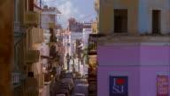 High angle zoom out Old San Juan street scene through archway /  San Juan, Puerto Rico