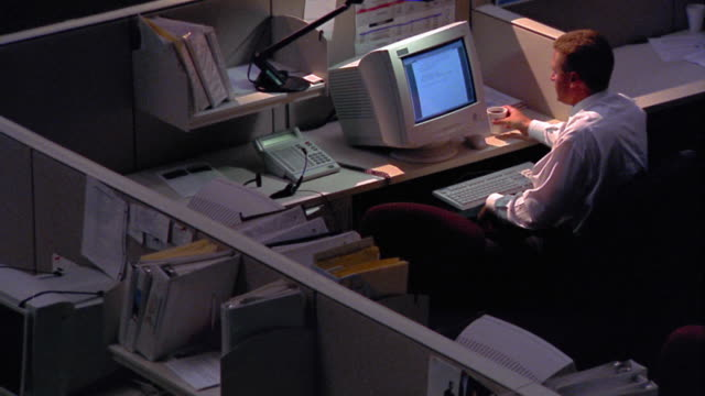 high angle zoom out one man working late at computer with desk lamp in dark office with cubicles