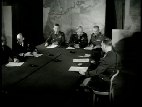 High Command at table w/ map BG General Dwight D Eisenhower talking w/ Field Marshall Bernard Montgomery at table RAF Air Marshall Arthur Tedder...