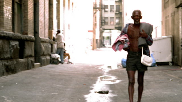 High contrast mature Black man in open shirt (homeless) walking in alley toward camera / Los Angeles