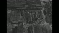 High flight over destroyed towns and countryside of Japan after World War II bomb raids and atomic bombs / Nagasaki destroyed Mitsubishi factory /...