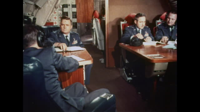 High ranking military officers do paperwork on a plane