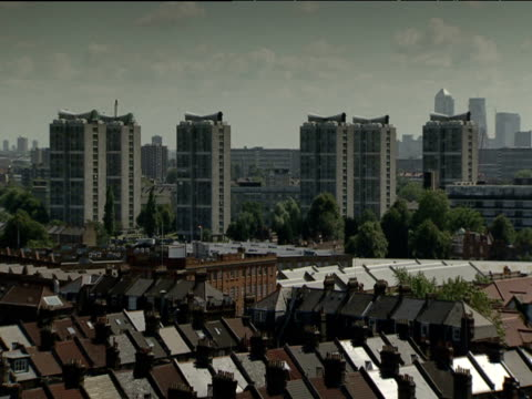 High rise flats stand amongst urban sprawl Canary Wharf stands in background London