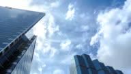high rise office building under cloud sun sky time lapse