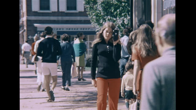 HD High School Band playing while walking woman w/ small boy putting fingers in ears VS Teenage female walking w/ transistor radio to ear girl...