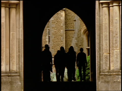 SILHOUETTE high school / college students walking under archway of school / England