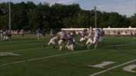 High school football players on field in white jerseys blue helmet player running football to end zone for touchdown gets tackled toward end Sports...