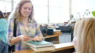 High school girl checking out books at library checkout counter with library ID card
