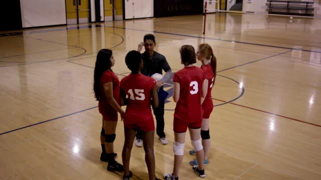 High-School-Mädchen-Volleyball mit Trainer
