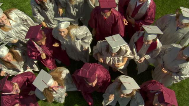 WS HA SLO MO High school graduates (17-19) jumping up toward camera / Appleton, Wisconsin, USA
