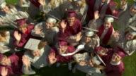 WS HA SLO MO High school graduates (17-19) waving at camera and giving high fives / Appleton, Wisconsin, USA