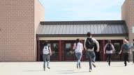 High school students running into school