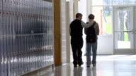 A high school teacher encourages a student as they walk along an empty hallway.
