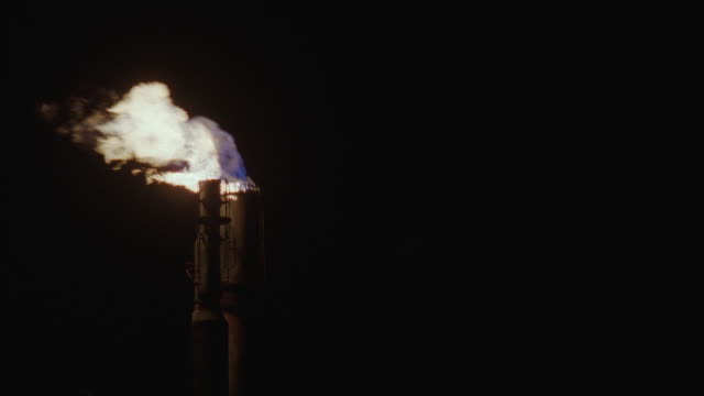 MS, LA, High section of chimney in oil refinery against night sky