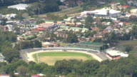 High shot of Bulli Showground and racing complex Woolworths Supermarket Bulli Station suburban housing rooftops and traffic along Princes Highway /...