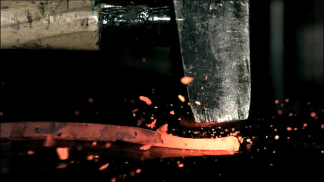 High speed anvil iron with hammer, glowing hot